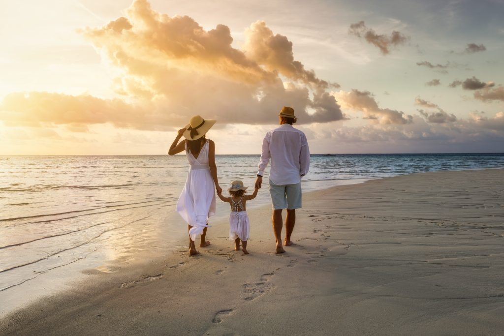 couple and young child walking on the beach